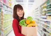 stock photo of local shop  - Beautiful young Asian woman shopping in a grocery store - JPG