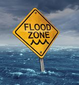 stock photo of hazard  - Flood warning concept with a yellow traffic sign flooded with water on a dangerous dark stormy cloud sky as a symbol of insurance risk and weather hazards as a natural disaster - JPG