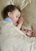 stock photo of girly  - Portrait of toddler child boy or gir sleeping under a blanket in a bed - JPG