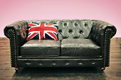 image of puffy  - Black Chesterfield couch with union jack cushion in emty room with wooden floor and pink background - JPG