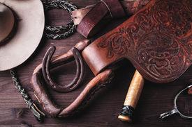 foto of western saddle  - horse saddle leather and various equipment on background - JPG