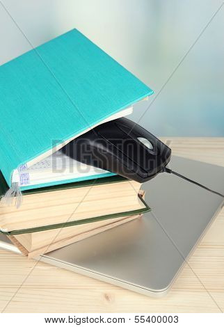 Computer mouse on books and notebook on wooden table on room background