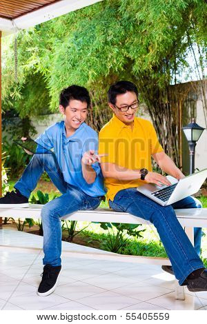 Chinese father talking with his son, they enjoying the leisure time together with a tablet computer and laptop