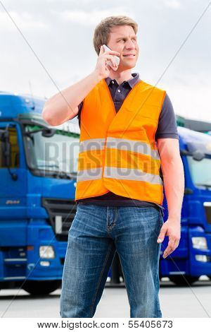 Logistics - proud driver or forwarder with mobile phone in front of trucks and trailers, on a transshipment point