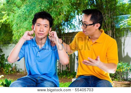 Chinese Asian father talking to his son but he will not listening, holding his ears with his hands refusing the good advice