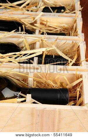 Wooden case with wine bottles close up