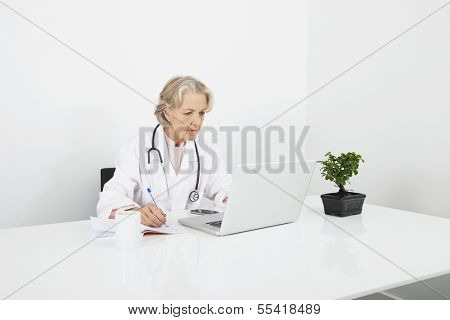 Senior female doctor writing notes while looking at laptop in clinic