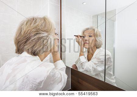 Senior woman applying eyeliner while looking at mirror in bathroom