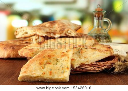Pita breads on wooden stand with oil on table on bright background