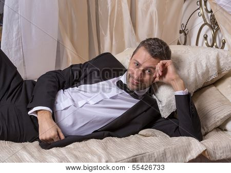 Elegant Playboy Reclining On A Bed