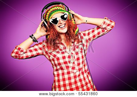 Portrait of a cheerful girl listening to music in headphones.