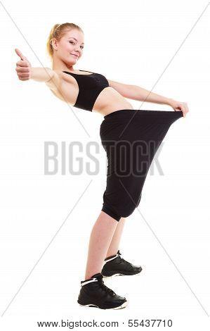 glückliche Frau zeigen, wie viel Gewicht sie verloren, große Hose