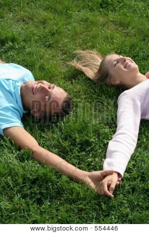Couple Lying On Grass