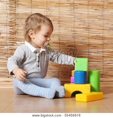 Little kid playing with toy blocks.