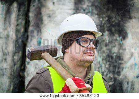 Man with sledge-hammer near old wall