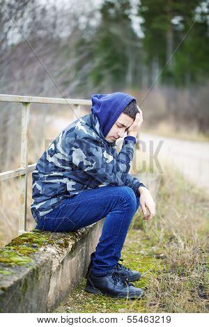 Sorrowful boy on the bridge near road