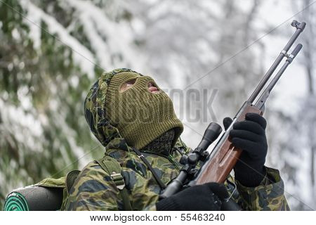 Hunter with optical rifle in winter in the woods