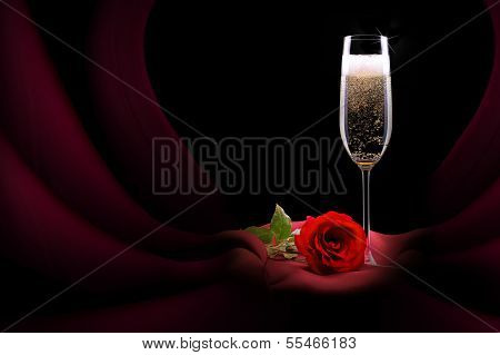 champagne glass on black and red silk with flower
