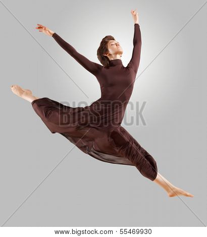 Girl dancing in a dark dress with a gray background. isolate