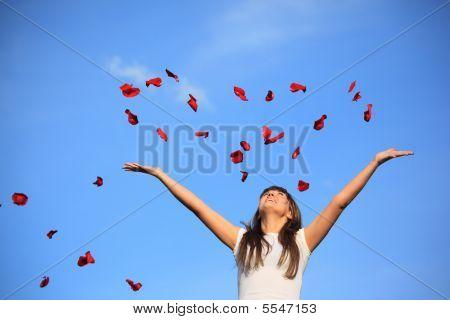 Menina espalha pétalas de rosa contra o céu
