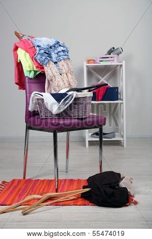 Heap of  clothes on color chair,  on gray background