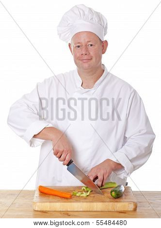 Male Chef Chopping Vegetable On A Chopping Board