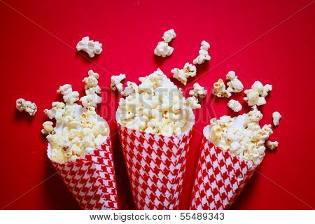 Three containers full on popcorn on a red background