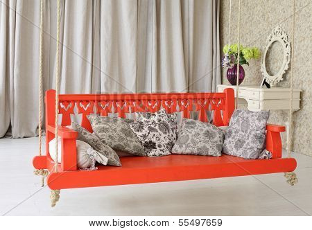 Big red wooden swing with pillows and  console mirror in stylish light studio.