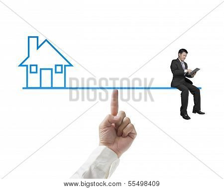Businessman Sitting On Seesaw Balance With Home