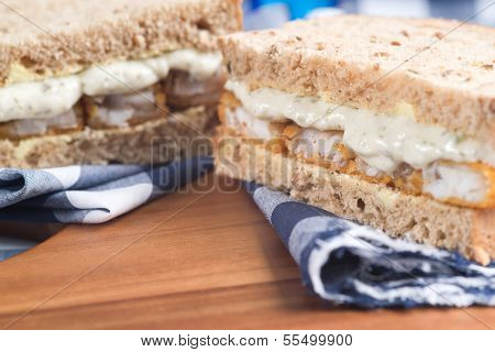 Fresh Fish Finger Sandwich On Wholegrain In Rustic Kitchen Setting