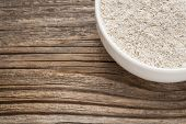 gluten free whole grain rice flour - a ceramic bowl on grained wood background