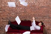 stock photo of settee  - Conceptual image of an elegant businessman lying relaxing on a settee against a brick wall with flying paperwork floating in the air above him - JPG