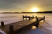 picture of dock a lake  - Amber Colored Sunrise above a Jetty on a Frozen Winter Lake with Ice and Snow