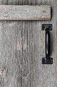 pic of woodgrain  - Distressed rustic barn wood door with handle as textured background - JPG