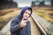 image of middle finger  - Boy showing middle finger at outdoor on the railway - JPG
