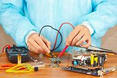 Master checks board of electronic device with a multimeter in service workshop