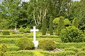 stock photo of graveyard  - Graveyard with white cross at Olsker round church on the Danish island Bornholm - JPG