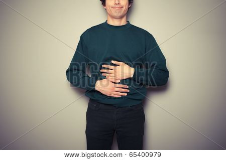 Young Man Rubbing His Stomach
