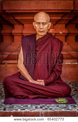 YANGON, MYANMAR - JANUARY 3, 2014: Ascetic Buddhist monk meditating in Shwedagon Paya pagoda. Buddhism is major religion of Myanmar and belongs to Theravada branch