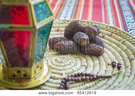 Close up of an arabic dates, lantern and prayer beads