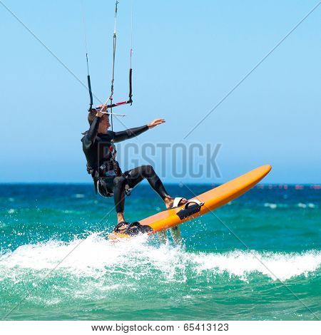 young sportsman kite sergfer on clean beach  in summer day