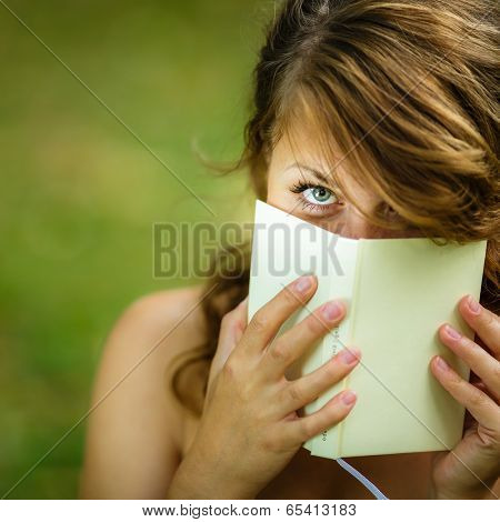 Cute young woman  covering her face with a book she is reading