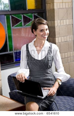 Pretty young woman with laptop in waiting room