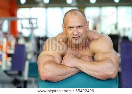 Smiling bodybuilder basing on fitness equipment in gym hall after training