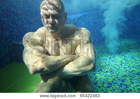 Bodybuilder with closed eyes on bottom of pool underwater among small bubbles