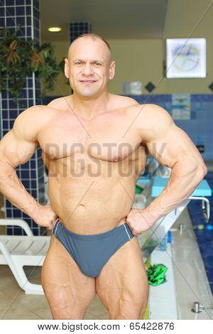 Happy sunburnt bodybuilder stands near indoor pool in big modern gym hall
