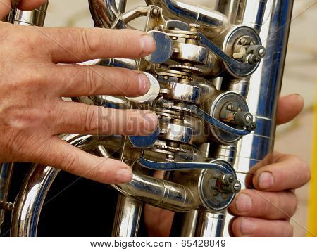 fragment of tuba with hands of musician