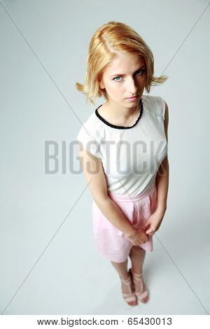Compassionate young girl standing on gray background
