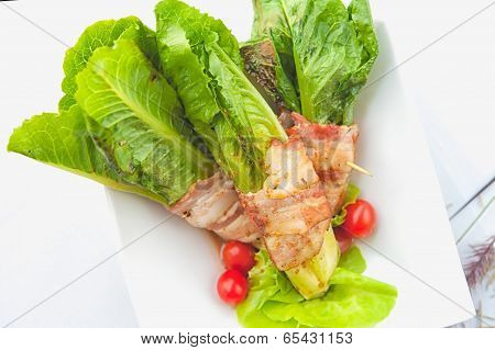 Green Cos Wrapped In Bacon On White Dish