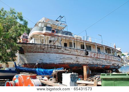 SYMI, GREECE - JUNE 18, 2011: Lazy Days, a former excursion boat, lays crumbling in the boatyard at Harani on the Greek island of Symi. It has has been there for 19 years due to an ownership dispute.